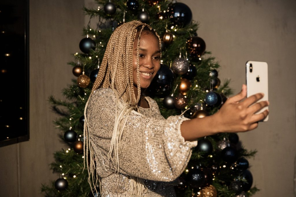 woman in white long sleeve top standing beside a christmas tree