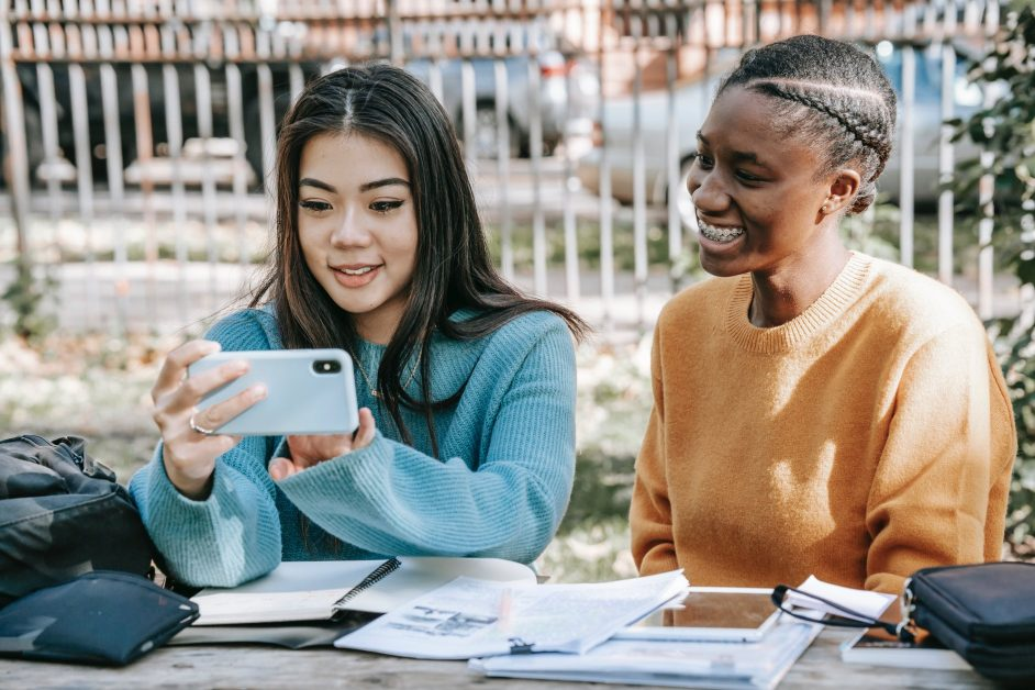 glad multiethnic women making video call with smartphone